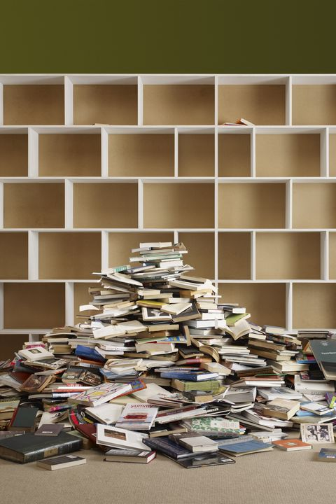 pile of books by empty shelves