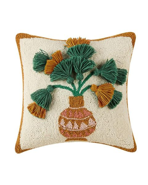 pillow with a design of a pot with green and gold flowers coming out of it made of yarn
