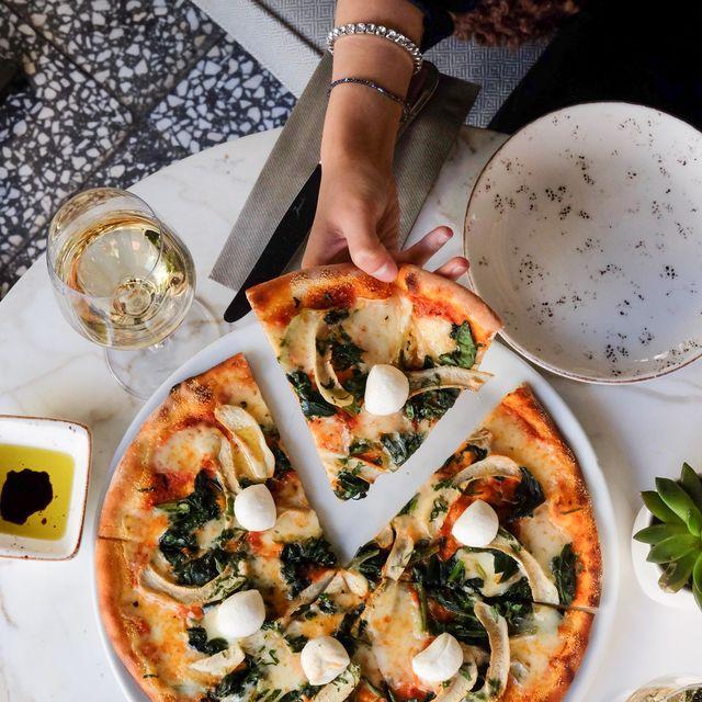 mujer cogiendo un trozo de pizza