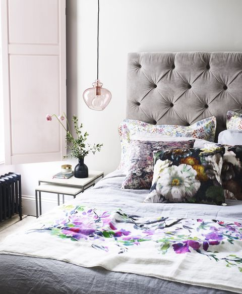 light and airy bedroom with grey quilted bed frame and floral cushions and pink window shutters