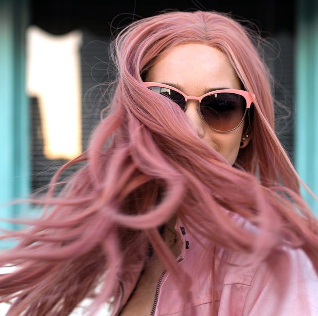 woman in sunglasses shaking out long pink hair