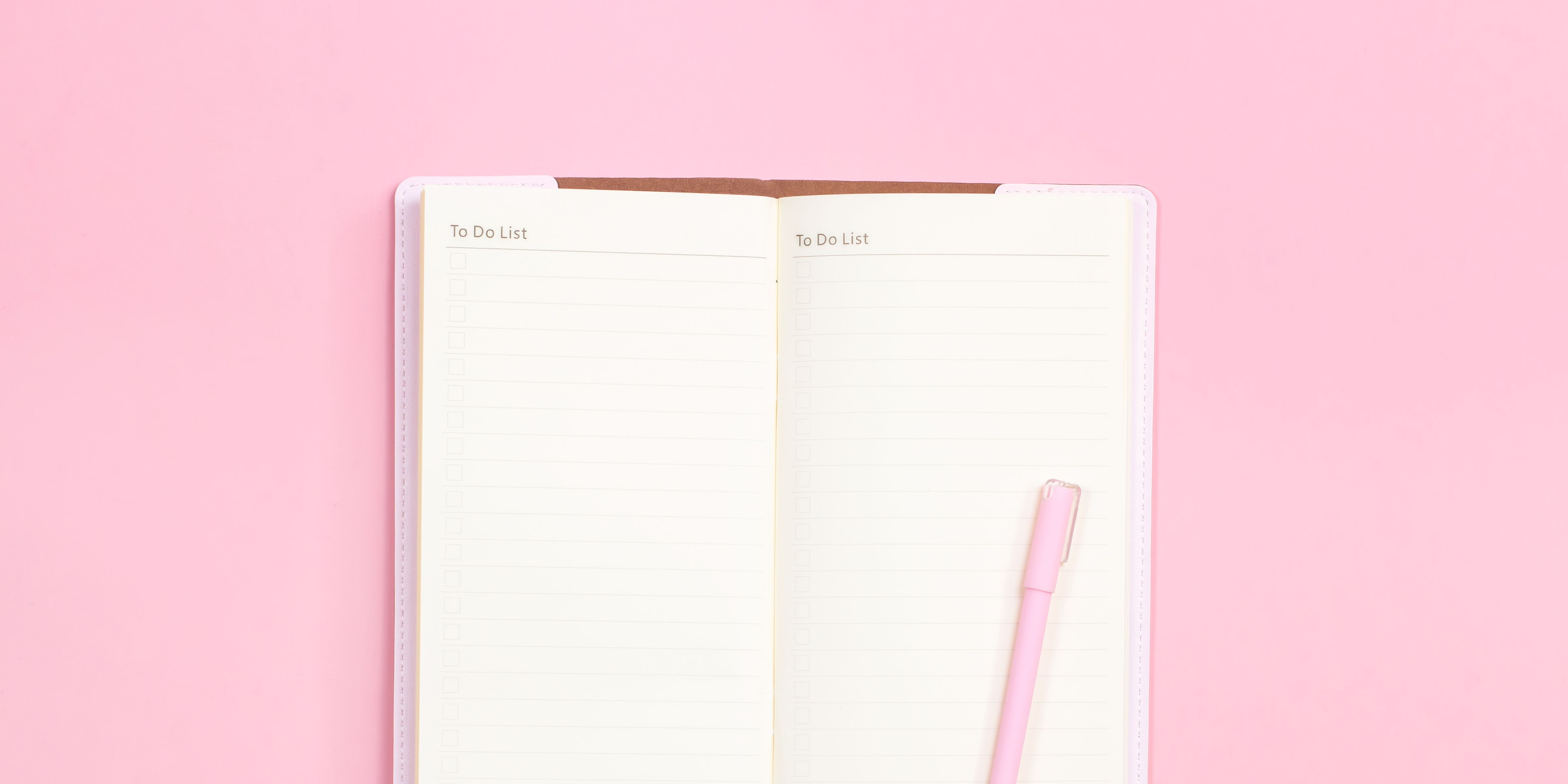 Pink notebook and pen to take notes on top of pink pastel desk.