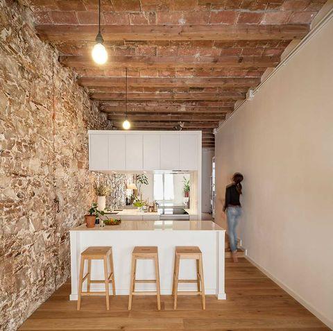 un piso en barcelona con paredes de piedra y decoración japonesa