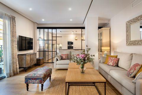 salón abierto a la cocina decorado en tonos neutros con alfombra de fibras