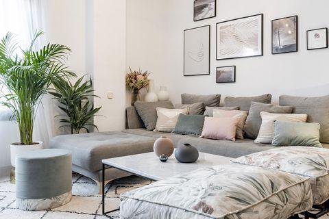 salón de estilo nórdico y boho con sofá gris con chaise longue y cojines en colores pastel