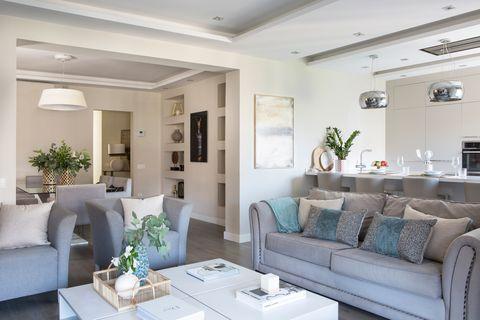 salón comedor abierto a la cocina y decorado en tonos grises y blancos