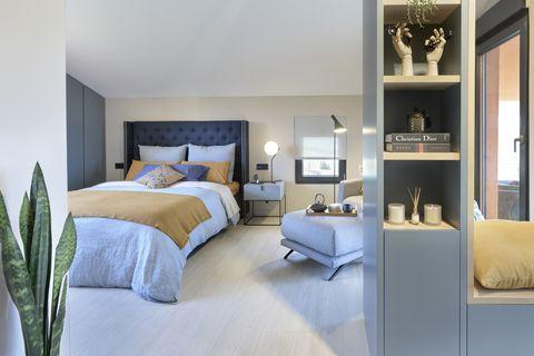dormitorio abierto decorado en azules, grises y mostazas
