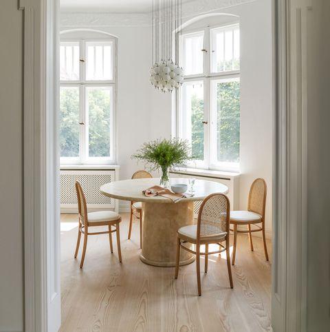comedor con mesa redonda de mármol, sillas de madera y lámpara suspendida con bolas