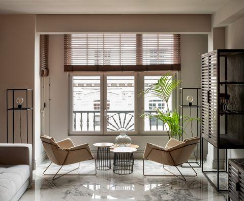 salón con suelo de mármol y dos butacas de diseño contemporáneo como rincón de lectura