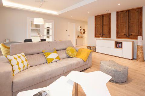 salón abierto a la cocina decorado con estilo nórdico en tonos grises y mostazas