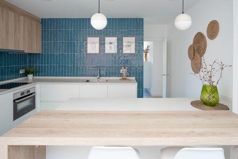 cocina con azulejos azules y barra de desayunos de madera