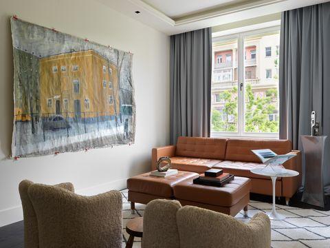 salón moderno con sofá de piel capitoné a juego con los reposapiés y tapiz sobre la pared