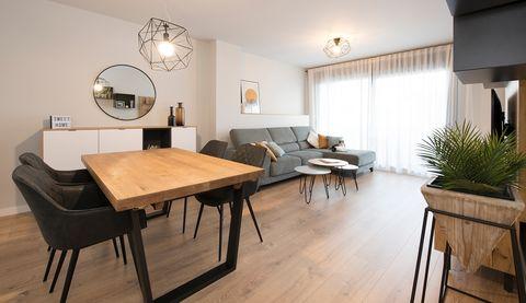salón comedor decorado en tonos grises con mesa de comedor de madera