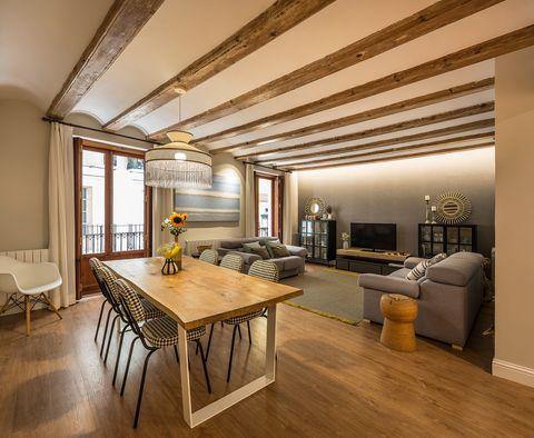 salón comedor decorado en tonos neutros con vigas de madera vistas