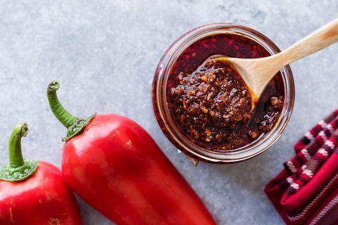 rode peper op tafel met een potje hete saus erbij