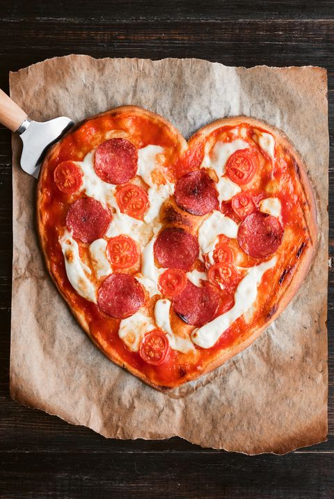pizza in the shape of heart. lying on a paper for a baking and wood table made of ebony