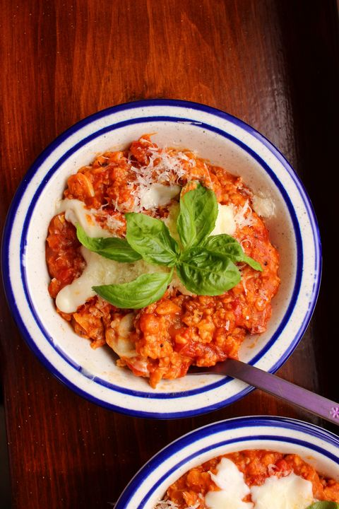 "a bowl of red tinged tomato based ""pizza"" flavored oatmeal topped with mozzarella and parmesan, with a sprig of basil"