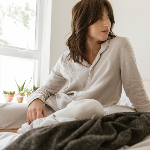 Sitting, Skin, Bed sheet, Nightwear, Comfort, Textile, Leg, Neck, Bedding, Hand,