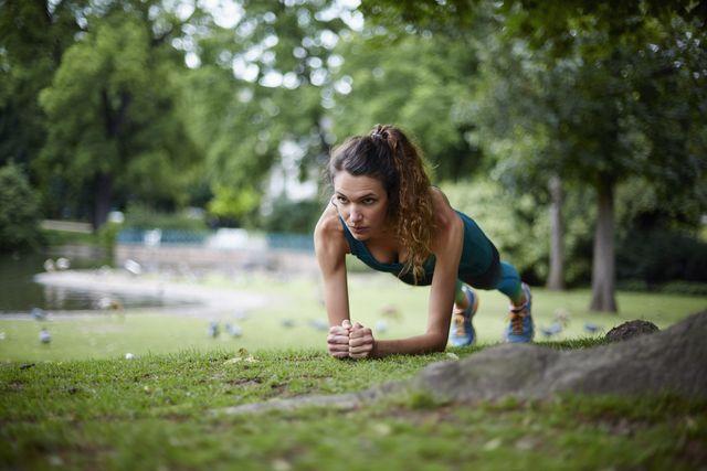 vrouw sport in park doet oefening planken
