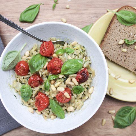 Pâtes Orzo Au Pesto, Tomates Cerises, Pignons De Pin Et Basilic Sur Une Table En Bois Et Avec Une Miche De Pain Sur Le Côté
