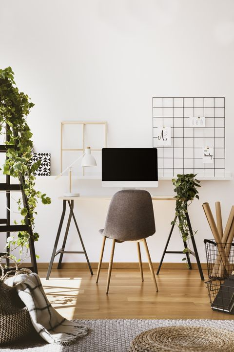 plant, white lamp and desktop computer on desk in freelancer's interior with grey chair real photo