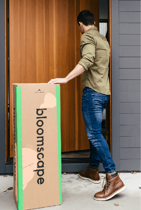 Man in front of door with a Bloomscape box