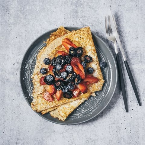 a plate of crepes with berries on gray background