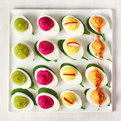 a plate of deviled eggs on dark grey stone background top view