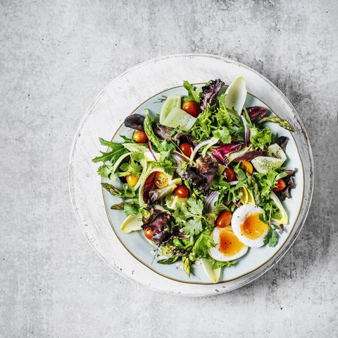 a plate of fresh salad on gray background