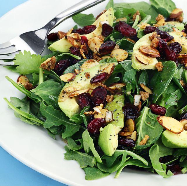 a plate of healthy avocado almond spinach salad