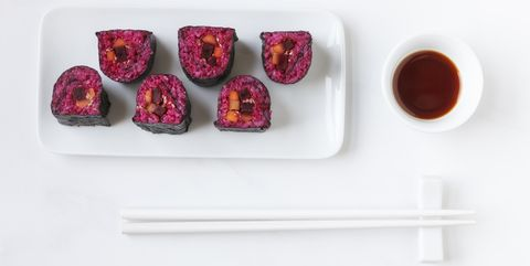 Plate of Maki Sushi, bowl of soy sauce and chopsticks on white ground