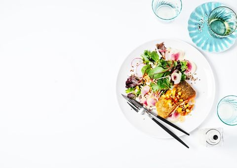 a plate of seared salmon and fresh salad on white background