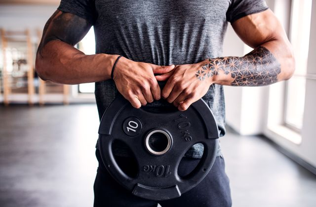 portrait of attractive sportsman with heavy dumbbell plate in fitness club