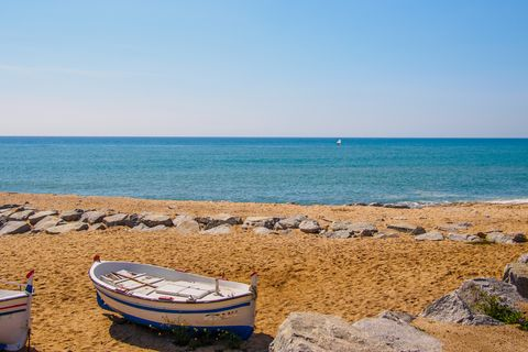 coastline with boat on the sand and another boat