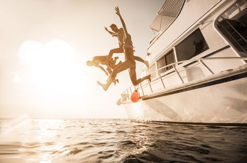 playful people jumping from the boat into the sea
