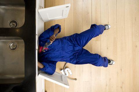 Plumber working under kitchen sink, overhead view