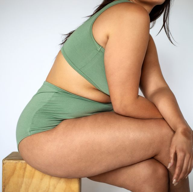 plus size woman in lingerie sitting on a stool