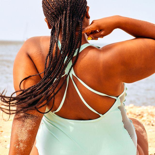 woman sitting on beach in blue swimsuit