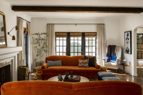 living room, orange couch, white walls, white curtains