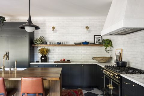 sarah solis kitchen, black cabinets, white subway tiles, wooden island, tan leather bench stools