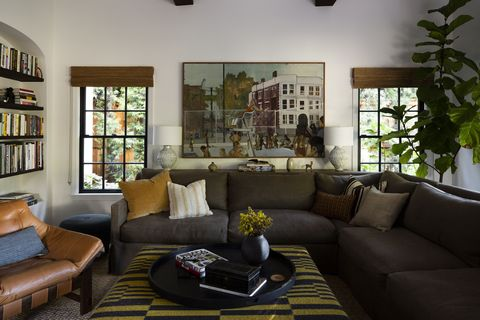 sitting room, green couch, leather chair, yellow pillow, white walls