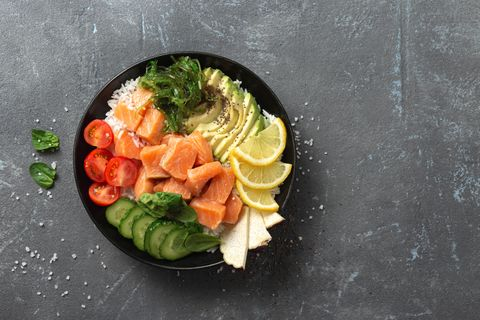 bowl with salmon, avocado and vegetables top view