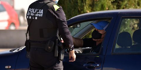 a police officer wearing a face mask verifies the