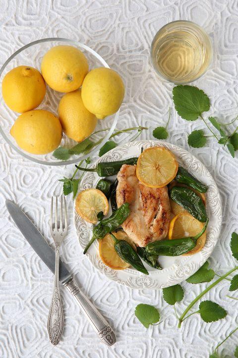 una fuente con limones junto a un plato con pollo, limones y pimientos