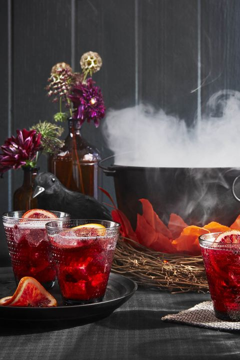 red pomegranate cocktails on a halloween decorated table