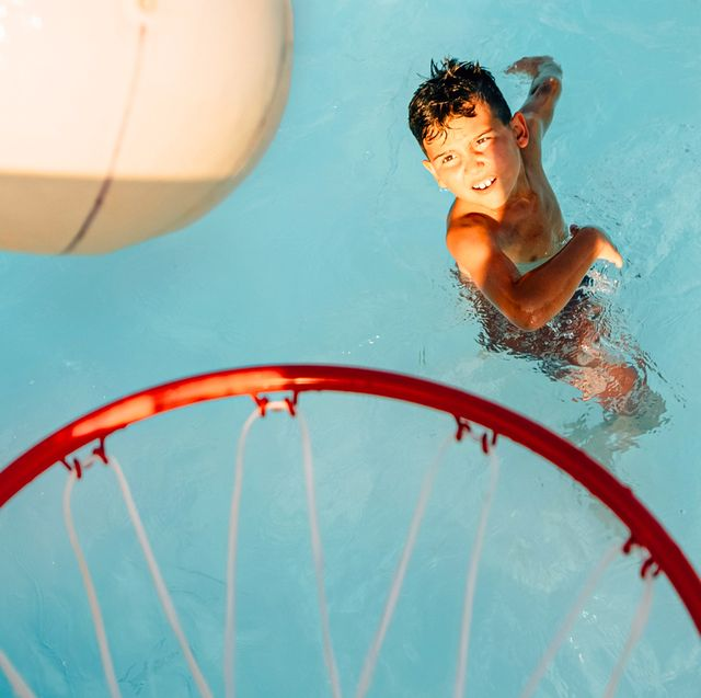 boy playing basketball in pool