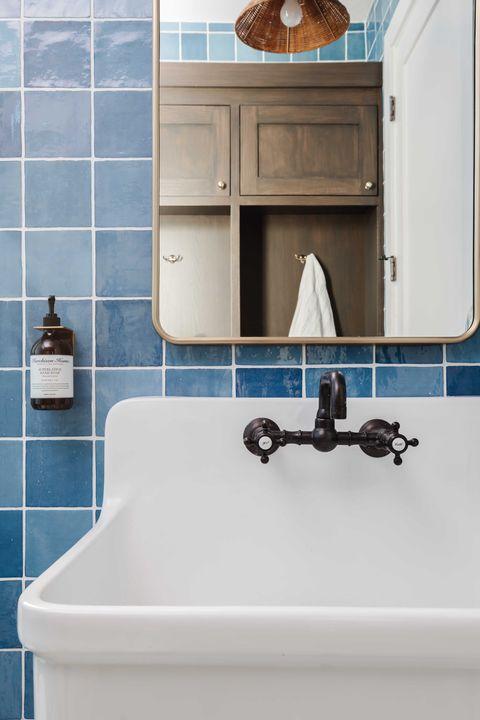 bathroom, blue tiles, white kitchen sink, black faucet