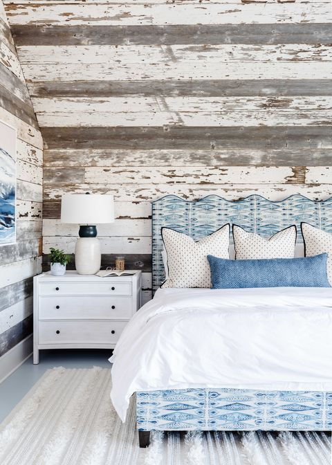 bedroom, wooden wall panelling, blue and white bed frame with white linen sheets
