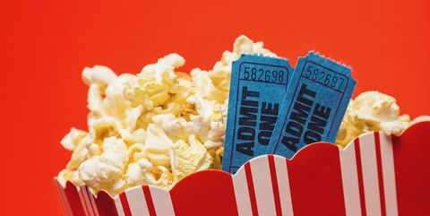 Popcorn And Movie Tickets With Numbers In Container Against Red Background