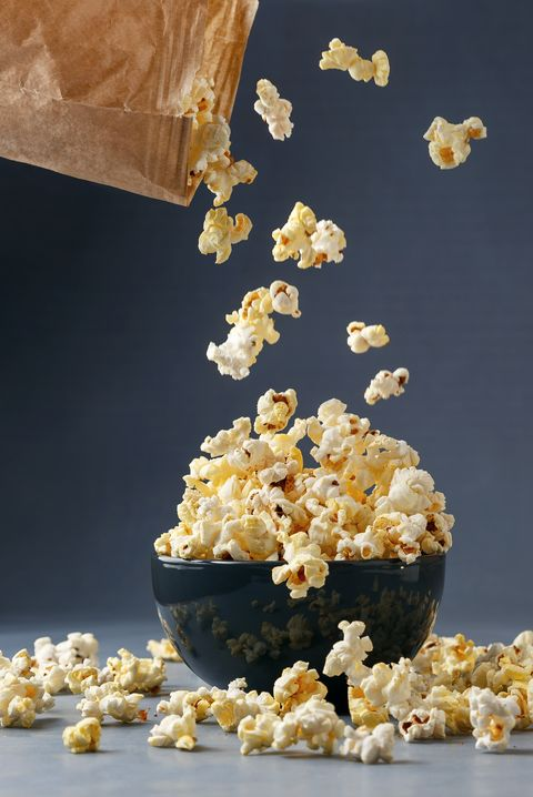 Popcorn flying into the bowl over grey background